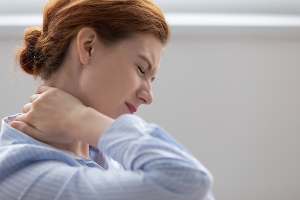 Woman Touching Her Neck Because Of Neck Pain